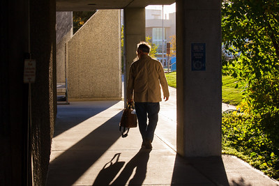 Campus photographer Todd Paris walks toward his office in Eielson Building on a sunny September morning.  Filename: CAM-12-3550-5.jpg