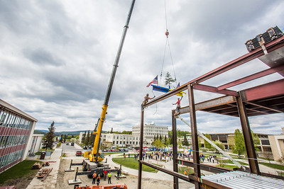 Iron workers with Davis Constructors prepare to place the final steel beam into position in UAF's new engineering facility this afternoon while a crowd of university, legislative and business leaders look on. The final piece of steel is topped with Alaska and U.S. flags and, following an ancient  Scandinavian tradition, a small tree.  Filename: CAM-14-4199-106.jpg