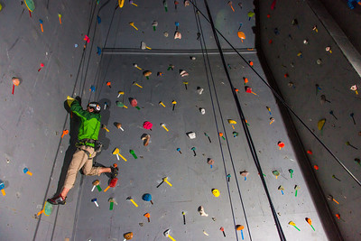 A climber chooses his route during an evening event on UAF's climbing wall.  Filename: CAM-13-3925-74.jpg