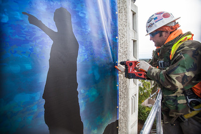 Jonathon Houx attaches a bolt to secure a large banner on a side of the Gruening Building.  Filename: CAM-13-3921-11.jpg