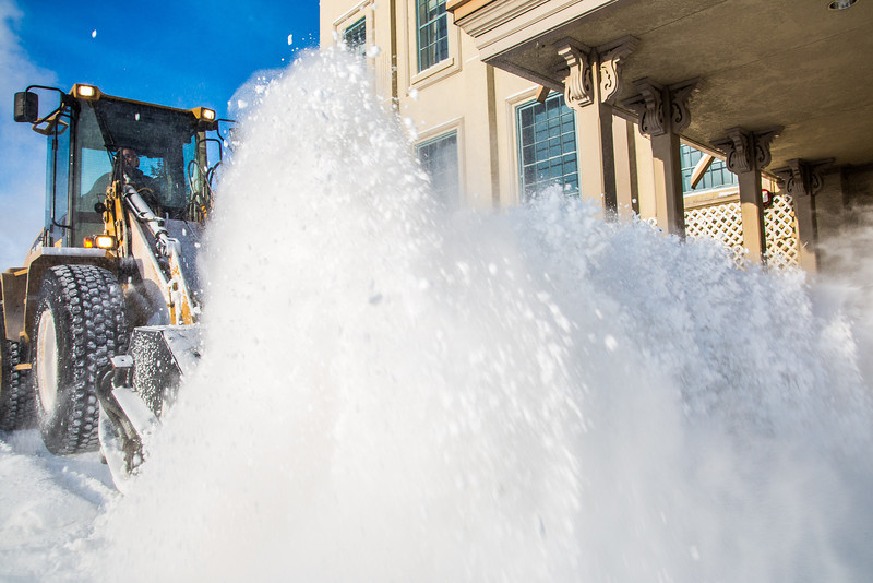 """A Facilities Services crew member uses some heavy equipment to sweep the sidewalk in front of Signers' Hall after a late winter snowfall.  <div class=""""ss-paypal-button"""">Filename: CAM-13-3786-13.jpg</div><div class=""""ss-paypal-button-end"""" style=""""""""></div>"""