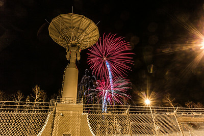 Fireworks illuminate the Alaska Satellite Facility's 11-meter antenna on West Ridge during the annual New Year's Eve Sparktacular.  Filename: CAM-13-4028-55.jpg