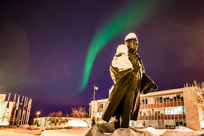 A strand of light from the aurora borealis floats above the statue of Charles Bunnell and the Bunnell Building on the Fairbanks campus.  Filename: CAM-13-3724-9.jpg