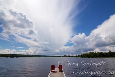 Sunset cottage dock muskoka chairs rain storm coming