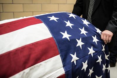 American flag drapes casket of Veteran