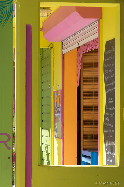 Shop front through a side panel in Les Saintes.