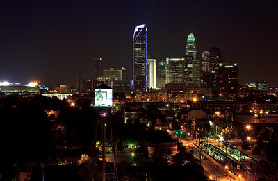 Charlotte Skyline at night.  Panthers stadium on the left, Duke Energy Tower lit up in blue, Bank of America Tower, Southend Water Tower, train tracks in the middle.