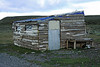 Woodplank siding, corrugated tin roof and door, and plastic windows of a fishing camp cabin - northwestern Tierra del  Fuego province - Magallanes region.