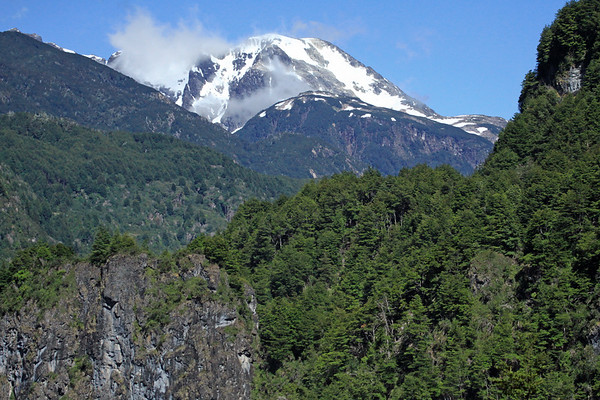 Across the glacial formed rocky slopes, clustered with southern beech trees, of the Magellanic Subpolar Forest ecoregion - to the slopes of Cerro Cono Negro, up in the clouds - the Rio Simpson National Reserve.