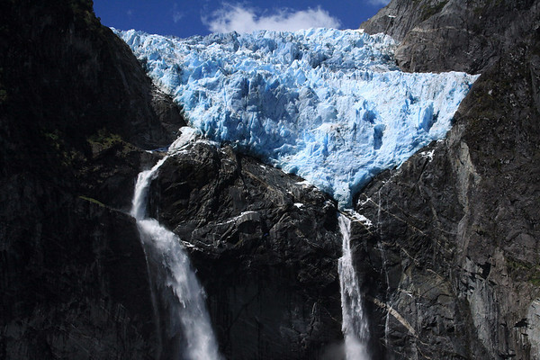 Sunlight upon the blue hue of terminus snout ice, of the Ventisquero Colgante - early summer season, with the two plunge falls and a cascade/ribbon falls, descending the igneous rock - Queulat National Park.