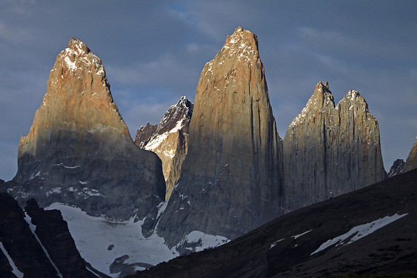 Early morning sunlight upon the Towers of Paine - with the sunlit Cerro Fortaleza, distal between Torre Sur and Torre Central - and Torre Norte, displaying its twin peaks - and a slight glimpse of Cerro Escucio beyond.