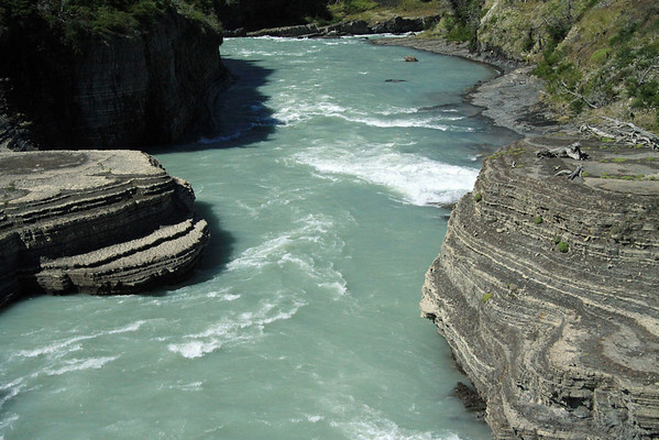 Rapid water below the Rio Paine Waterfall, among the sedimentary rock.