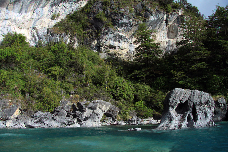 Metamorphic marble outcrops, along the western shoreline of Lago Carrera, revealing its Patagonia vegetation and glacial milk water.