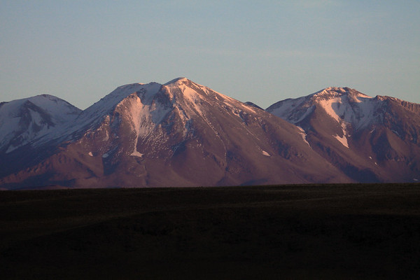 Early morning light upon Volcan Aucanquilcha - with its peak (c), distal along the mostly shaded ridge.
