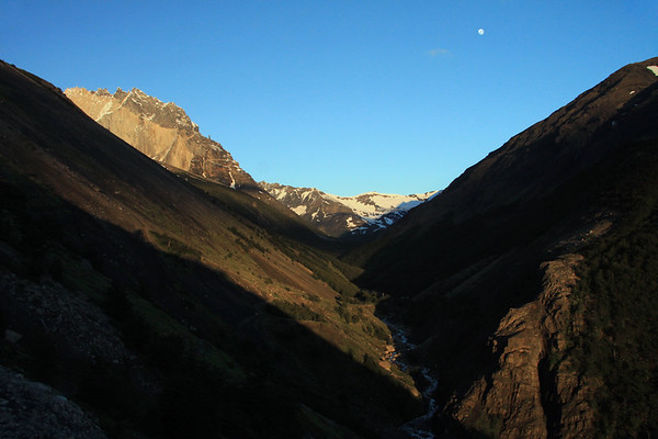 Sunlight and shadows along the Valle Asencio - to the sunlit Cerro Nido Condor (l) - the Cerro Oggioni, along the distal horizon, at the confluence with the Silence Valley and the waning gibbous moon in the naked sky.