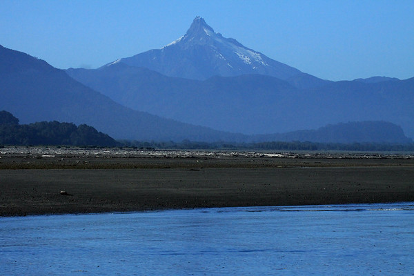 Beyond the Rio Yelcho, and the alluvial plain, scattered with driftwood - to Volcan Corcovado - Los Lagos region.