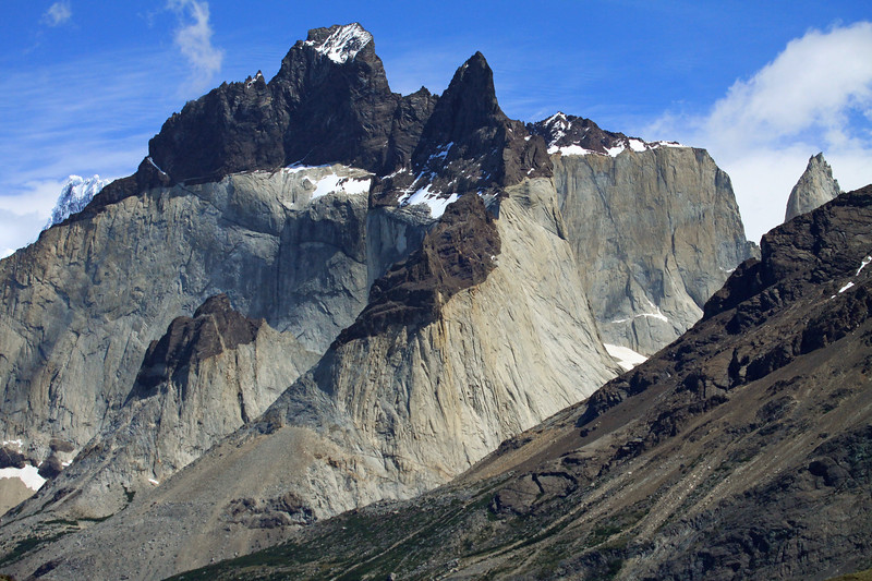 Across the southern vegetated slope of Mt. Almirante Nieto - to the metamorphic hornfels cap rock, of the Horns of Paine, Cuerno Este (c) beyond to Cuerno Principal (l), and Cuerno Norte (r) - distally to the peak of La Mascara (r) and Cumbre Principal, of Cerro Paine Grande (distal, l).