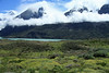Across the Patagonia Steppe ecoregion vegetation - beyond the glacial milk/flour water of Lago Nordenskjold - above the stratus cloud, to Mt. Almirante Nieto (r) - Horns of Paine (c), Cuernos Este and Principal - and Cumbre Principal (l), the highest point of Cerro Paine Grande, as well as the Torres del Paine National Park.