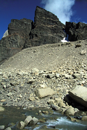 Across the glacial water - up the lateral moraine - to Cerro Nido Condor, and the snow-covered glacial ice between the couloir (a narrow eroded gully within a steep gradient in a mountain terrain).