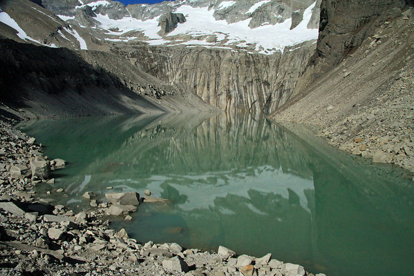 Reflection of the the base of the Towers of Paine and glacier, upon the calm water, surrounded by glacial till.