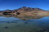 Morning's totally placid and tranquil reflection of Cerro Pastillitos, rising to about 16,700 ft. (5,090 m) - upon Laguna Santa Rosa - with the distal snow-capped Volcan Copiapo (a stratovolcano), also called Cerro Azufre (sulfur) - all below the naked Puna sky above.
