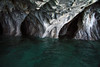 Water sculpted marble sea cave rock - joins the glacial milk water of Lago Carrera.