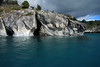 Marble sea caves and overhangs - along the western shoreline of Lago Carrera - revealing its glacial rock flour water and southern beech trees.