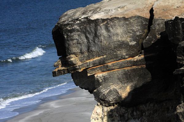 Sandstone sea cliff ledge - down to the waves breaking along the sandy shoreline of Bahia Moreno.