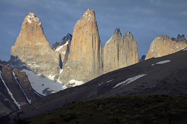 Early morning sunlight upon the glacial sculpted, Torres del Paine - Torre Sur (l), with the mostly shadowed glacier at its igneous granite base - beyond Sur's shaded northern buttress, to the cloud-shaded metamorphic caprock of Cerro Fortaleza - Torre Central, and the adjacent Cerro Norte, with its slightly shadowed twin peaks - between the gap to the distal Cerro Escucio peak - Cerro Nido Condor (r), revealing the jagged granite peak, and lower hornfels ridge, of Cerro Nido Condor - foreground beyond the cushion plants, the shaded slope of Cerro Paine (r) and Mt. Almirante Nieto (l), displaying its glacial ice streams and slightly sunlit slope.