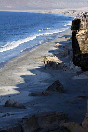 Jagged sea cliff ledge shadows, cast along the shoreline of Bahia Moreno, among the sandstone outcrops, wave formed kelp-lines, kelp gulls, and breaking waves - with the lower slope of Morro Moreno, in the distance.