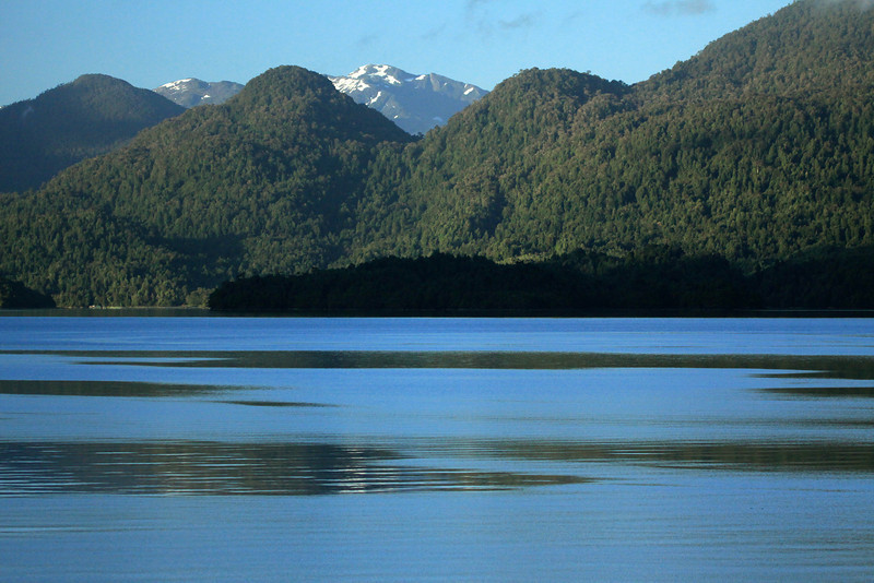 Moning reflection upon the water of the fjord Seno Ventisquero - and glacial formed and now forested and ice patched slopes, of the Patagonia Andes - Aisen region.