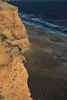 Late evening sunlight upon the sedimentary sandstone cliff, rising about 130 ft. (40 m), above the waves and rocky shoreline of Bahia Moreno.