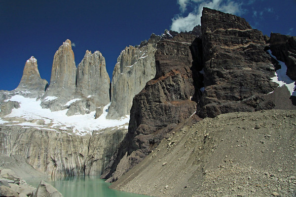 Torres del Paine (Sur, also known as D'Agostini - Central - and the twin peak of Norte, also called Monzino) - adjacent is Cerro Nido Condor, among the clouds, and its lower metamorphic rock slope ending along the lateral moraine, adjacent to the glacial milk or rock flour water - then beyond the reflection of the glacial melt water streak upon the rock, up to the snow-coated glacier.
