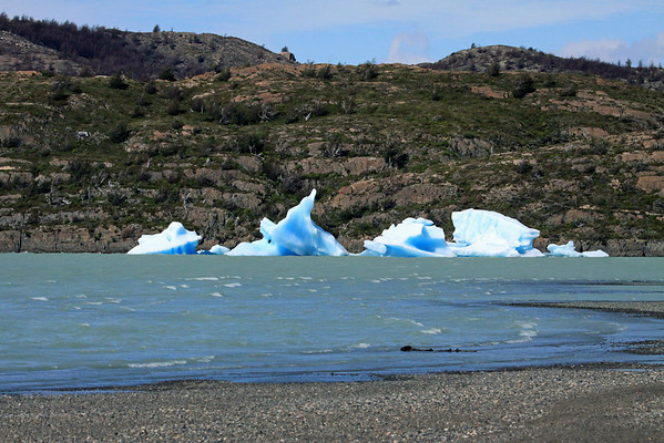 Across the waves breaking along the southern shoreline of Lago Grey - to the weather and water sculpted bergy bits (glacial ice measuring from 3-15 ft./1-5 m above the water surface.