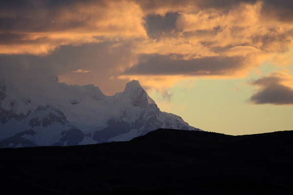 Sunset light upon the cumulus clouds, above the shaded hanging glacier, along the Cordillera Andes, the Southern Patagonia Ice Field (Campo de Hielo Sur).