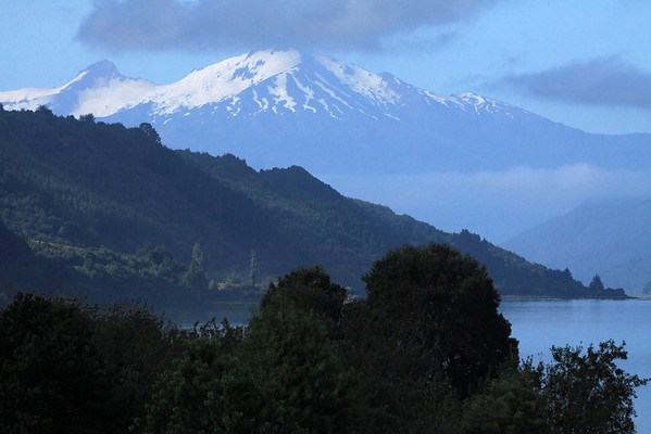 Along the northeastern forested slope of the Reloncavi Fjord - to the distal glaciated stratovolcano, Volcan Yate, rising about 7,175 ft. (2,187 m) - while the average depth of this glacial carved fjord averages around 560 ft. (170 m) deep, along its 34 mi. (55 km) length and average width near 2 mi. (3 km).