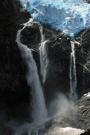 3) Calving of the Ventisquero Colgante - between its plunge waterfalls, among the igneous rock.