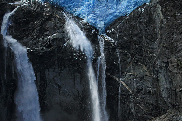 1) Calving of the Ventisquero Colgante - airborne glacial ice fragments, free-falling with the glacial milk water, of the adjacent plunge falls, among the igneous rock.