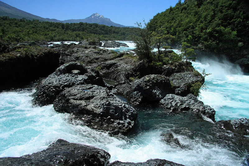 Petrohue Waterfall - displaying its glacial rock flour water, among the igneous rock and Valdivian vegetation - to the distal Cerro Picada, revealing its glacial ice streams.