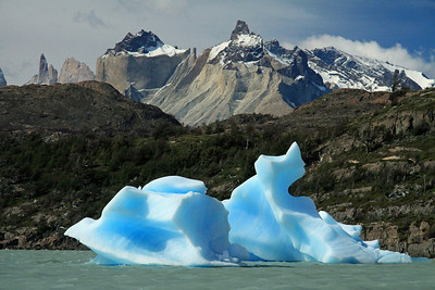 Weather and water sculpted bergy bit - across the rocky and vegetated peninsula, the transition between the Patagonia Steppe and Magellanic Subpolar Forest ecoregions - to Cuernos del Paine (Horns of Paine), adjacent to Hoya (blade) and Espada (sword) - with Mt. Almirante Nieto (distal, r).