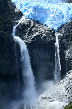 Glacial ice of the Ventisquero Colgante - plunge waterfalls and mist upon the plutonic igneous rock - Queulat National Park.