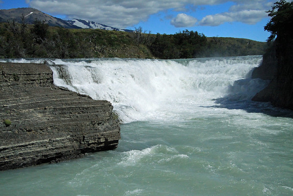 Beyond the cushion plant, growing from the sedimentary rock - to the upper crest or brink, of Cascada del Rio Paine (a cascade falls) - Torres del Paine National Park.