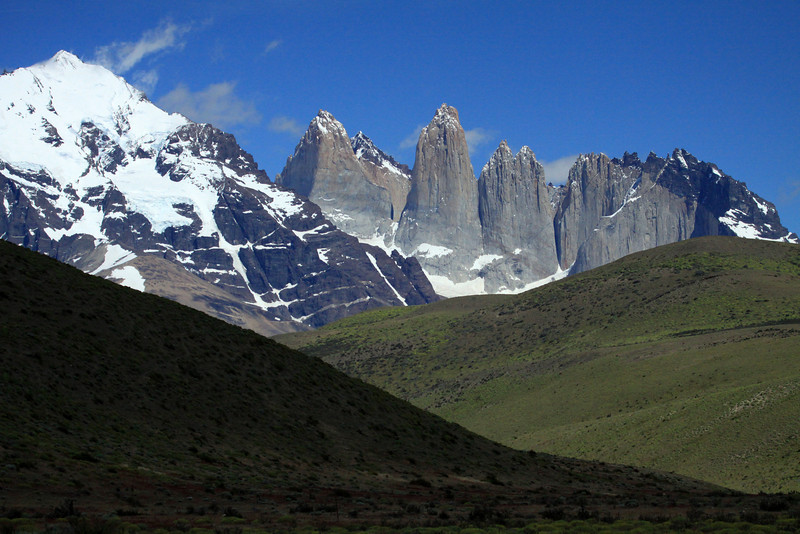 Beyond the cloud-shaded and sunlit slopes, during the early summer season - to Mt. Almirante Nieto (l), to the granite spires of the Towers of Paine, and the adjacent hornfels (metamorphic rock) capped Cerro Nido Condor - with a distal view of Cerro Fortaleza (between Torre Sur and Central), and Cerro Escudo (between Torre Norte and Cero Nido Condor) - all part of the Paine Massif.