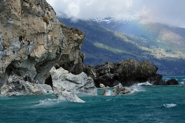 Eastern end of the metamorphic rock peninsula, the lower slope of Cerro Parras - this is the Marble Chapels Nature Santuary - the western shore of Lago Carrera - with a slight rainbow beam, along the rocky and forested slope and glacial ice of the Northern Patagonia Ice Field - just northwest of Puerto Tranquilo (village), Aisen region.