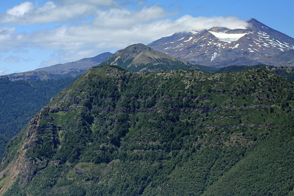 Over the Cordillera Thermas, and peak of Cerro Mora - to Volcan Tolguaca, displaying a glacier in the northwestern crater, and below a fumarole (geothermal vent) - Tolhuaca National Park.