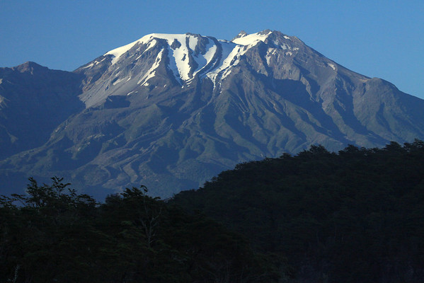 Volcan Calbuco - an active stratovolcano, an andesite volcano (extrusive igneous volcanic rock) - with a glacial ice cap, and peaking at around 6,572 ft. (2,303 m) - with the shadowed southern beech tree forest, in the foreground.