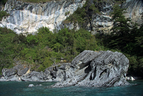 Metamorphic marble outcrops, along the Patagonia vegetation and glacial water shoreline, of Lago Carrera.
