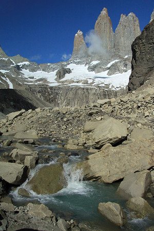 From the glacial water flowing from a lagoon below the Torres del Paine, beyond the clouds - with Cerro Nido Condor (r) - and La Hoya (l), the blade.