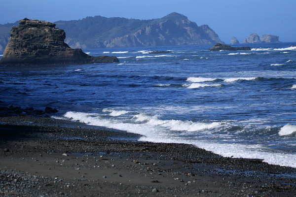 Southern shoreline of Bahia Cucao - beyond the sea stacks, to Punta Pirulil, rising about 400 ft. (120 m), above the western coastline of Isla Chiloé - and other water-sculpted sea stacks adjacent - here during late-ebb tide, with today a tidal range of about 18 ft (5.5 m).