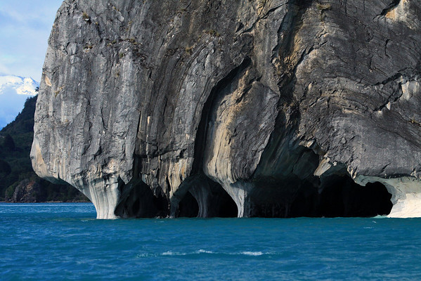 Sea caves along the metamorphic calcite marble of the Cathedral de Marmol (Marble Cathedral) - beyond the overhang, across the glacial flour water, to the western shoreline of Lago Carrera - and distally to the glacial ice along the slope, part of the Northern Patagonia Ice Field, and source water for this lake.
